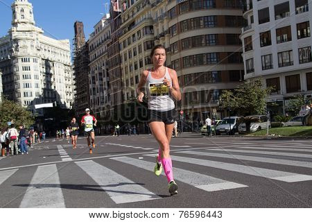 VALENCIA, SPAIN - NOVEMBER 16, 2014: Woman runner Yulia Smirnova of Russia competes in the 2014 Valencia Marathon.  Smirnova finished in 7th place (women division) with a time of 2:45:34.