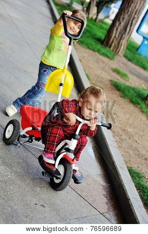toddler girl walking with baby sister on the tricycle poster