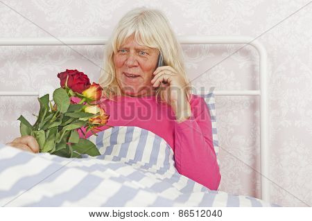 Cheerfull Woman In Bed With Roses And Telephone