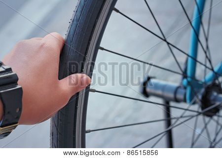 Wrings Hands On The Wheel Of The Bike.