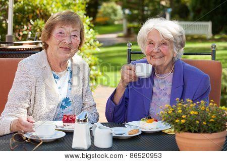 Senior Women Having Coffee At The Garden Table