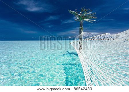 Empty over-water hammock in the middle of tropical lagoon in Maldives