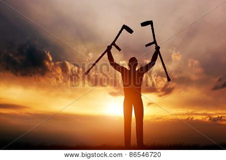 A disabled man raising his crutches at sunset. Positive concept of cure, recovery, medical miracle, hope, insurance etc.  poster