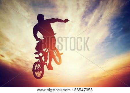Man jumping on bmx bike performing a trick against sunset sky. Extreme sport