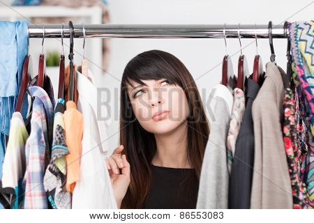 Beautiful Young Woman Near Rack With Clothes