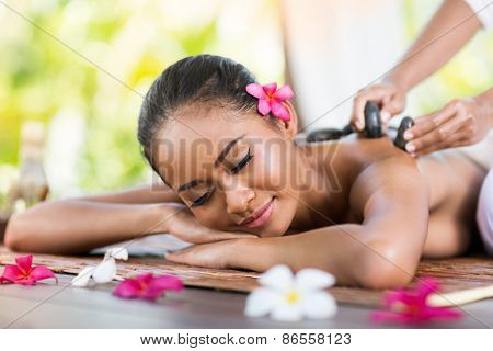young woman receiving massage of back with stone massage