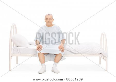 Mature patient in a hospital gown sitting on a bed and looking at the camera isolated on white background