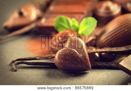 Chocolates background. Chocolate. Assortment of fine chocolates in dark and milk chocolate with vanilla and mint. Praline Chocolate sweets