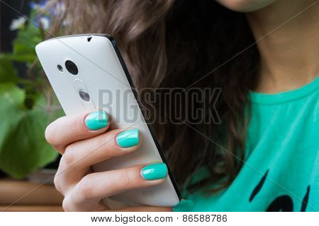 Female Hand With Bright Manicure Holding A Mobile Phone
