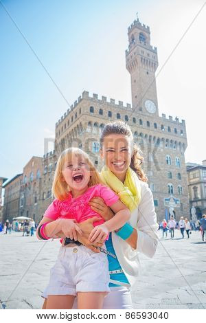 Portrait of smiling mother and baby girl in front of palazzo vecchio in florence italy poster