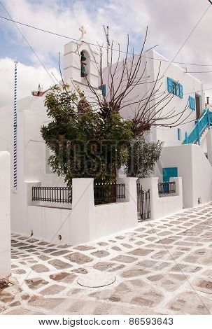 Classical greek church in town o Mykonos and tree.