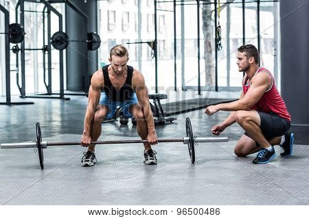 Trainer supervising a muscular man lifting a barbell