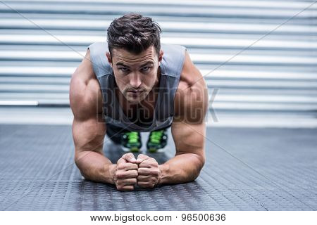 Portrait of a muscular man on plank position