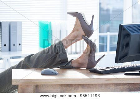 Businesswoman sitting on swivel chair with feet on desk at the office