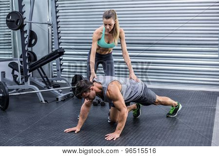 Female coach supervising a muscular man on a plank position