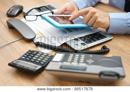 Busy Businessman  In Office With Full Of Accessories On Desk With Telephone Handset Off The Hook And