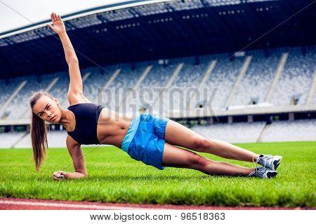 Fitness woman on stadium planking