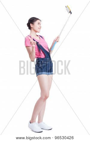 Young woman taking picture with smartphone selfie stick