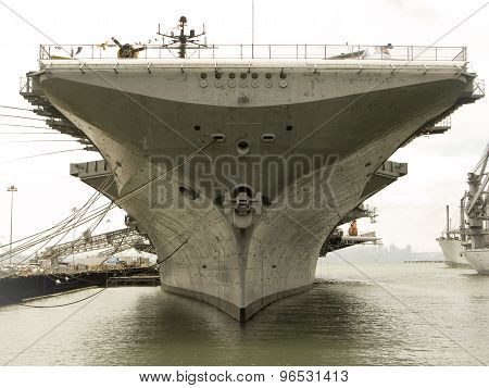Looking down the front of a docked aircraft carrier poster