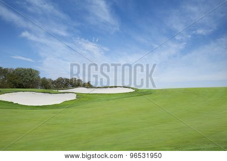 Green Golf Fairway With Sand Traps Below Blue Sky With Clouds