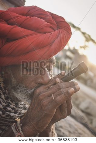 GODWAR REGION, INDIA - 14 FEBRUARY 2015: Elderly Rabari tribesman with red turban and blanket smokes chillum. Post-processed with grain, texture and colour effect.