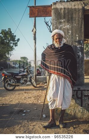 GODWAR REGION, INDIA - 14 FEBRUARY 2015: Elderly tribesman with walking stick, white turban and dark blanket. Post-processed with grain, texture and colour effect.