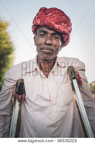 GODWAR REGION, INDIA - 12 FEBRUARY 2015: Rabari tribesman in field with crutches. Post-processed with grain, texture and colour effect.