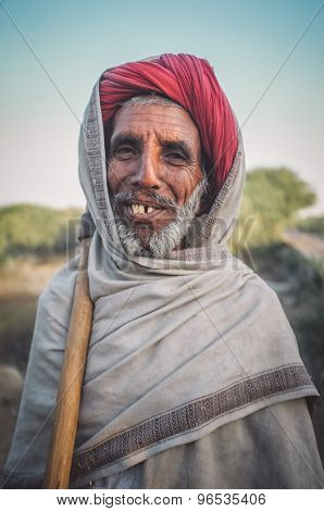 GODWAR REGION, INDIA - 14 FEBRUARY 2015: Elderly Rabari tribesman stands with ax on sholder. Post-processed with grain, texture and colour effect.