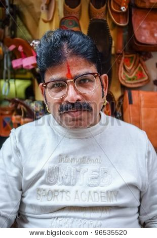 JODHPUR, INDIA - 07 FEBRUARY 2015: Store owner with mustache wearing glasses, gold earings and bindi sitting infront of shop. Rajasthan is known for leather designs than are sold around the country.