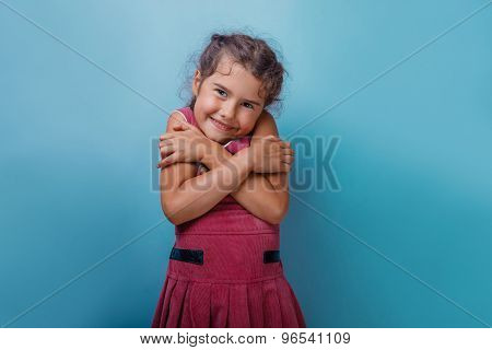 Girl European appearance decade hugging herself on a blue  backg