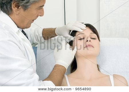 young caucasian woman receiving an injection of from a doctor