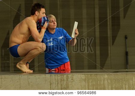 LONDON, GREAT BRITAIN - APRIL 25 2015: Tom Daley of Great Britain reviews a training dive with coach Jane Figueiredo  during the FINA/NVC Diving World Series at the London Aquatics Centre