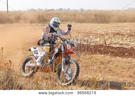 Motorbiker Thumbs Up Kicking Up Trail Of Dust On Sand Track During Rally Race.