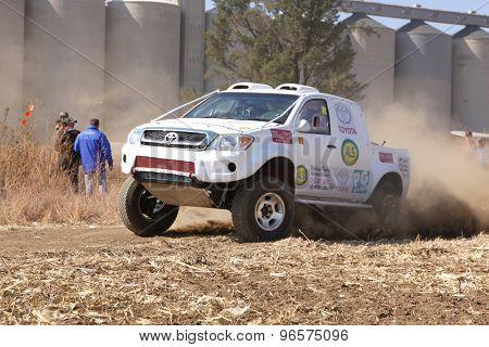 Drifting White Toyota Truck Kicking Up Dust On Turn Ar Rally.