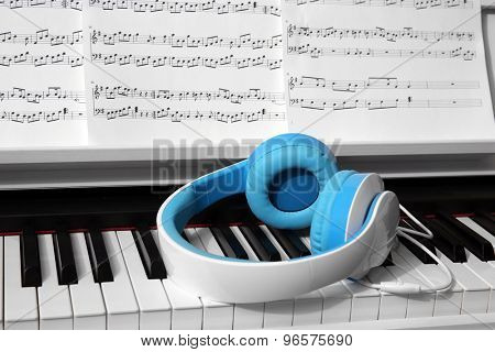 Piano with headphones and music notes close up