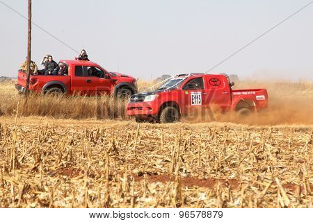 Red Toyota Rally Truck Passing Red Spectators Truck On Dusty Road.