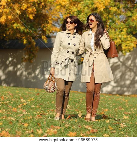 two attractive women in park at fall outdoors