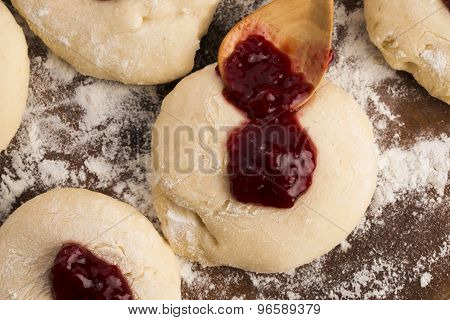 Dough with marmelade on wooden board, close up poster