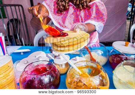Closeup traditional Colombian streetsnack oblea being prepared adding white sauce with top of jam an