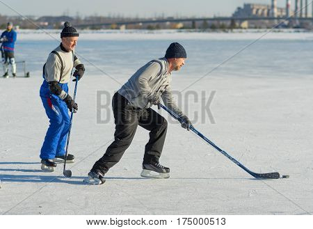 DNEPR UKRAINE - JANUARY 22, 2017: Mature amateur men playing hockey on a frozen river Dnepr in Dnepr city, Ukraine at January 22, 2017