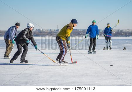 Dnepr Ukraine - January 22 2017: People of different ages playing hockey on a frozen river Dnepr in Dnepr city, Ukraine at January 22, 2017