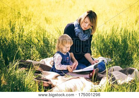 Portrait of happy family of two people on vacation. Young mother and little daughter read book sitting on picnic blanket in long green grass. Age of child 2 years and 4 month.