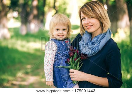 Portrait of happy family of two people on vacation. Young mother and little daughter posine for camera in beautifl spring garden. Age of child 2 years and 4 month. Horizontal color photography.