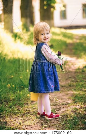 Portrait of happy little blond girl holding yellow bucket with tulip flowers. Cute funny child stands in sunny spring garden in countryside. Age of child 2 years and 4 month.