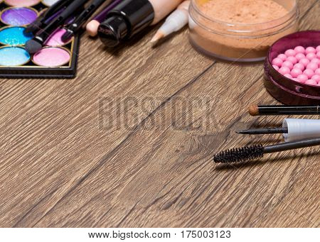 Frame of basic makeup products on wooden surface. Shallow depth of field, copy space