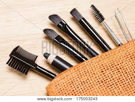 Accessories for care of brows. Brow comb, eyebrow pencil, angled brushes, tweezers, spooly brush in cosmetic bag. Eyebrow grooming tools