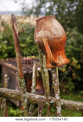 Old Traditional Ukrainian clay jug hanging on the fence