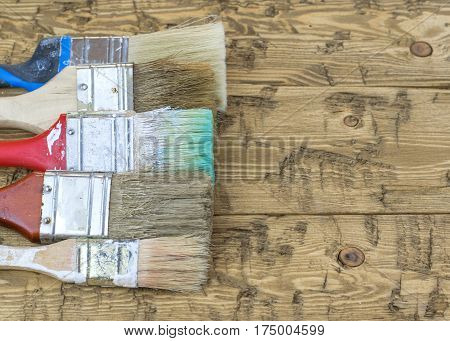 A set of old multi-colored brushes on a wooden table. Tools for wood tinting.
