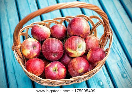 Ripe red apples in a basket on a blue board