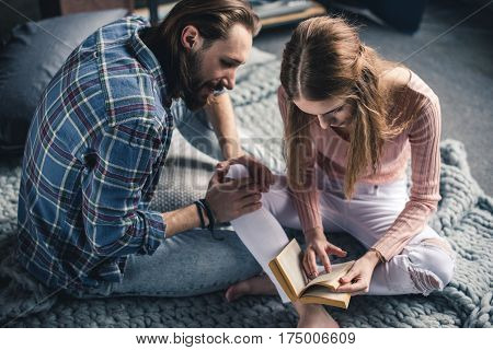 Young barefoot couple sitting on knitted blanket and reading book
